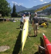 Rowing crew attending to boat on land in mountainous setting