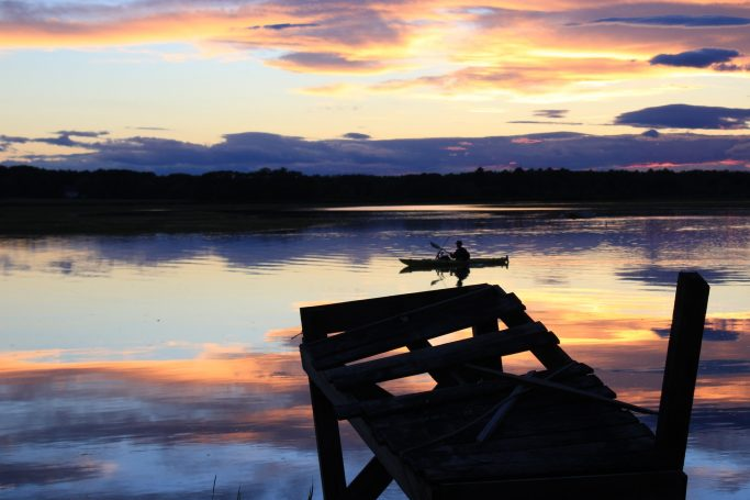 Rower on still water at sunset